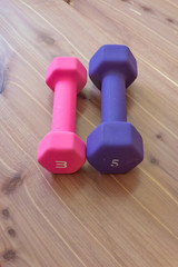 Pink and purple exercise hand weights side by side on a light wood background, copy space, vertical aspect