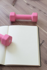 Two pink hand weights with open, blank journal, on a wood table top, copy space, neutral colors, vertical aspect