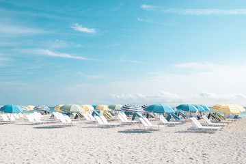 Sunny beach full of lounge chairs and umbrellas