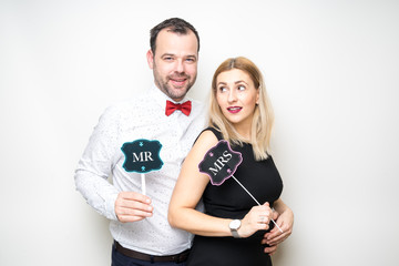 young couple funny props pose photo booth plain background