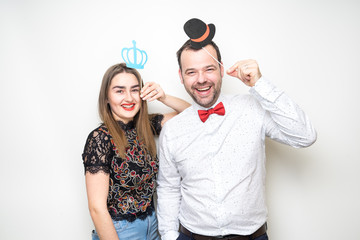 young couple friends pose photo booth funny props