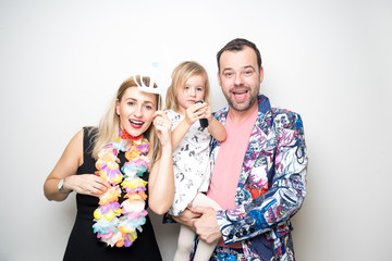 young family mom dad daughter pose photo booth funny props