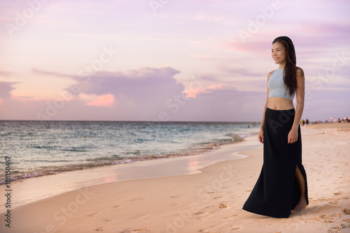 asian model woman walking on beach at sunset relaxing on luxury