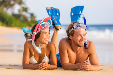 Beach holiday couple relaxing after snorkel swim happy with fins and diving mask. Summer travel lifestyle watersport leisure activity on holiday vacations.