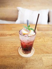 glass of strawberry juice with soda on wooden table
