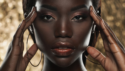 portrait of sensual young african woman against golden background
