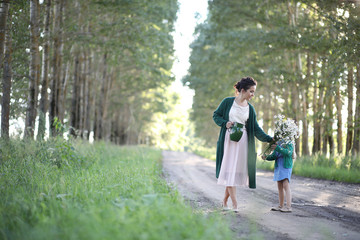 Mother with daughter walking on a road