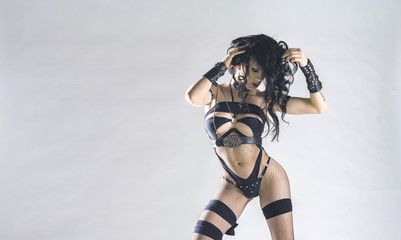 Sexy brunette woman in underwear with wet hair and whip, bdsm, isolated