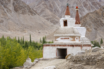 Buddhist chortens, white stupa and Himalayas mountains in the background near Leh in Ladakh, India