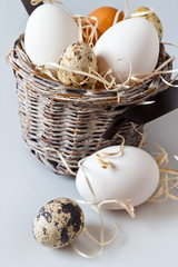 Czech traditional easter decoration - white chicken and quail eggs in a basket nest - village and rural atmosphere