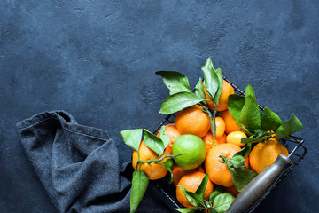 Tangerines or Clementines with Green Leaves in Basket on Dark Background. Top view and copy space for text