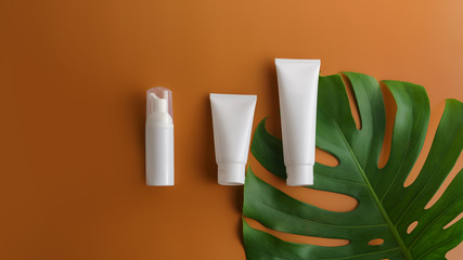White cosmetic products and green leaves on brown color background. Natural beauty product for branding mock-up concept.