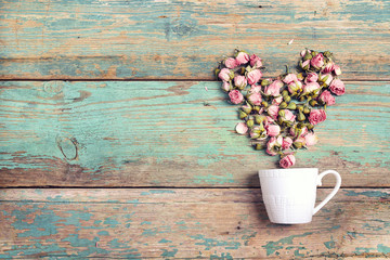 Coffee cup with heart from pink rose flowers coming out of it on old  turquoise wooden background. Copy space.
