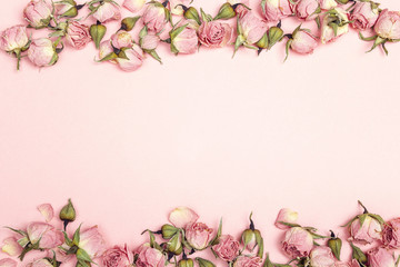 Border of small dry roses on pink background. Place for text.