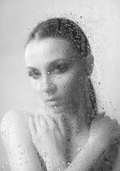 Brunette woman with makeup smoky eyes, folded his arms on the neck with water drops close-up on a light background black and white image