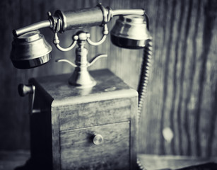 Old telephone and retro book on the desk. The phone of the past