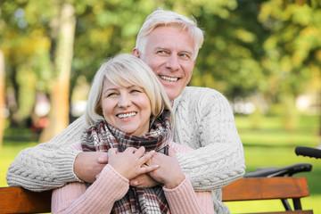 Cute elderly couple sitting on bench in autumn park