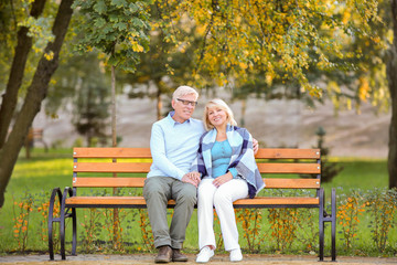 Cute elderly couple sitting on bench in autumn park