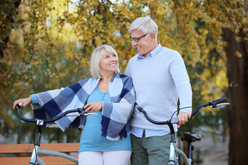 Cute elderly couple with bicycles in autumn park