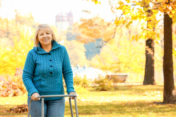 Senior woman with walking frame in park