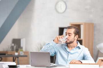 Young man drinking water in office