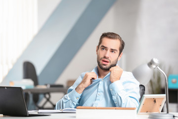 Young man suffering from heat in office
