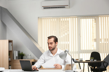 Young man working in office with operating air conditioner