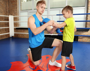 Trainer helping little boy put on boxing gloves in gym