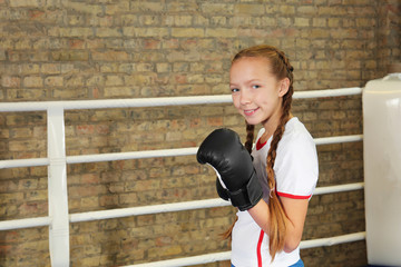 Adorable little girl in boxing gloves on ring