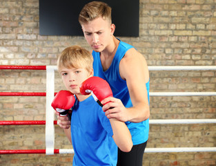 Little boy with trainer on boxing ring
