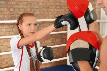 Little girl with trainer on boxing ring