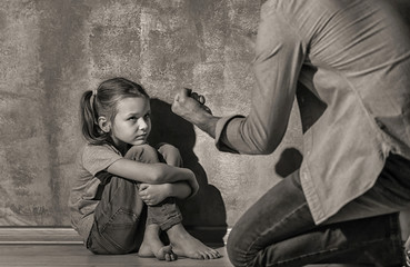 Man threatening his daughter indoors, black and white effect