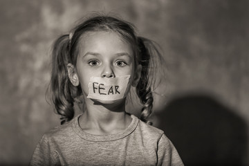 "Sad little girl with taped mouth and word ""Fear"" on grey background, black and white effect"