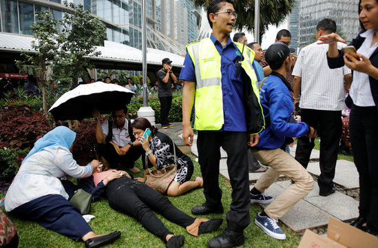 Injured people are treated outside the Indonesian Stock Exchange building following reports of a collapsed structure inside the building in Jakarta