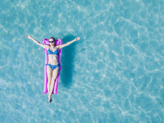 happy woman tourist on vacation, summer holidays on the beach, girl in bikini floating on the mattress in turquoise water of sea