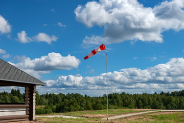 Pointer to the direction and strength of wind against the background of the sky