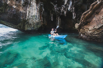 kayaker paddling in crystal clear water near the cave on Railay beach in Krabi, tourist travel on kayak in Thailand, blurred motion