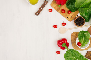 Border of fresh green greens, red paprica, cherry tomato, pepper, oil and utensils on soft white wooden background.