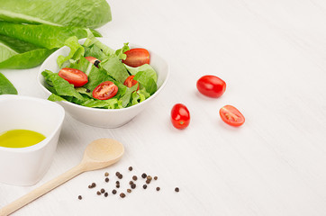 Healthy vegetarian spring salad -  fresh greens, tomatoes, pepper and olive oil on white wood background, closeup, copy space.