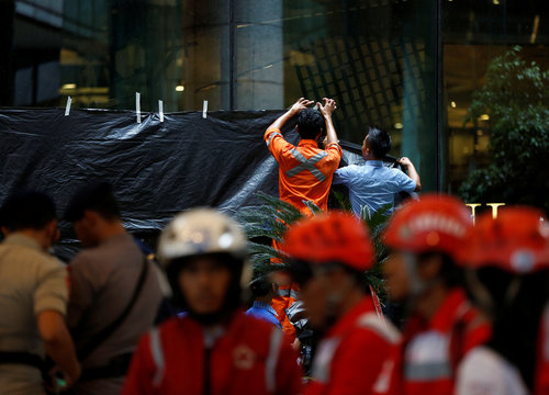 Workers cover a window to block the view inside a building at the Indonesia Stock Exchange following reports of a collapsed structure inside the building in Jakarta