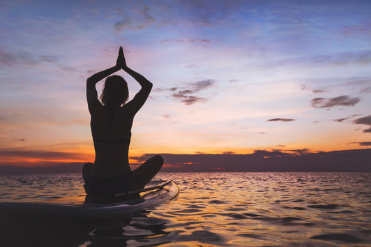 yoga on sup board, silhouette of woman on the beach