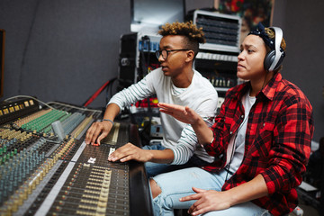 Young producer and singer sitting in studio of records and doing their work