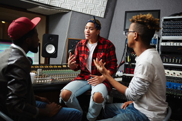 Sound operators talking to young musician in audio studio before recording songs