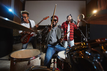 Band of young drummer, guitarist and singer playing instruments and performing songs in studio of records