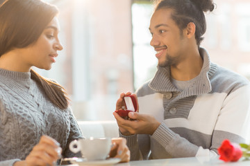 Young female looking at engagement ring in box held by her boyfriend who offering her to marry him