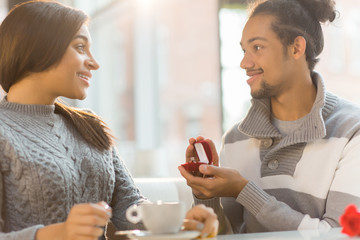 Surprised girl looking at her boyfriend with open ring-box with engagement ring inside