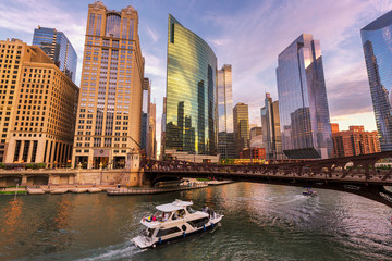 Chicago Downtown skyline and speedboat on Chicago river at sunset, Chicago, Illinois.