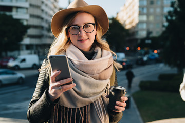 Sunny autumn day. Young attractive woman travels in hat and eyeglasses stands on city street, uses smartphone and drinks coffee. Hipster girl is looking for road. Vacation, adventure, trip.