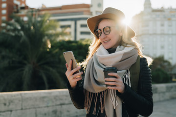 Sunny autumn day, backlight. Young attractive woman tourist in hat and eyeglasses stands on city street, uses smartphone and drinks coffee. Hipster girl is looking for road. Vacation, adventure.
