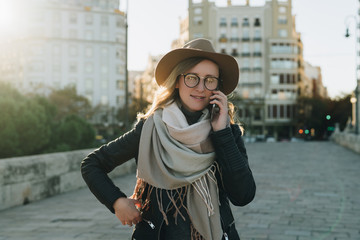 Sunny autumn day, backlight. Young attractive woman travels in hat and eyeglasses stands on city street, talking on cell phone, smiling. Hipster girl walks. Vacation, adventure, trip, traveling.